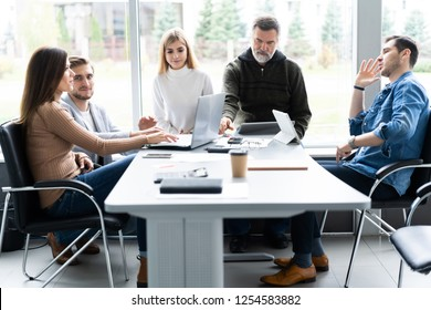Working day. Group of young modern people in smart casual wear discussing business while working in the creative office