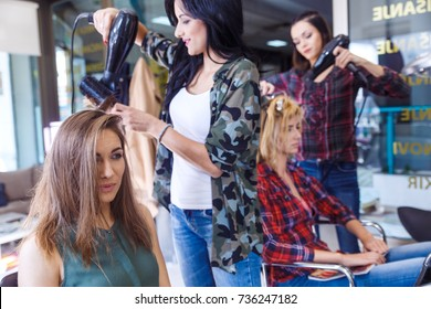 Working day inside the hair salon, hairdressers making hairstyle on two young woman.