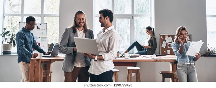 Working day in office. Group of young modern people in smart casual wear smiling and discussing something while working in the creative office