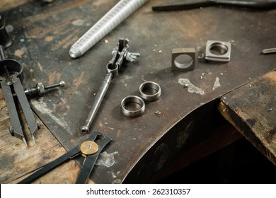 Working desk for craft jewelery making with professional tools. Still life of goldsmith's tools with rings.