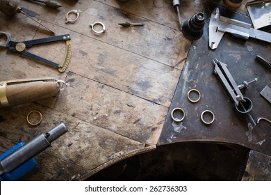 Working desk for craft jewelery making with professional tools. Grunge wooden table. View from above. Copy space.