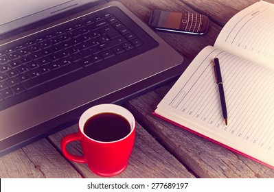 working desk with cup of coffee planner agenda laptop and mobile phone vintage morning photo