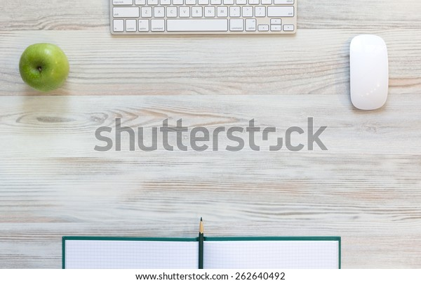 Working desk with green apple. View from above on light beige wooden working desk with green apple, large notepad, computer keyboard and mouse, green pencil
