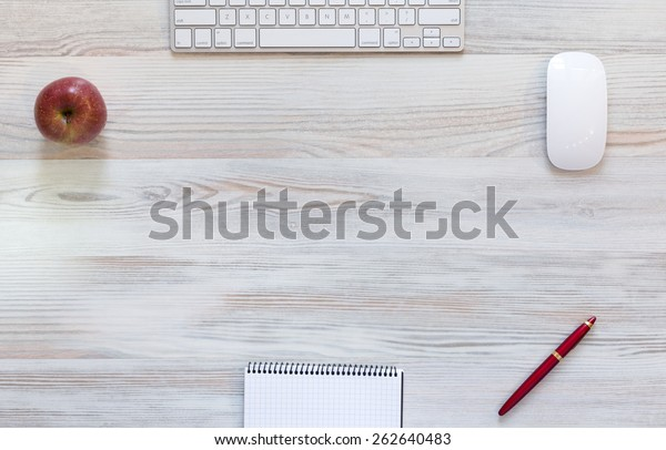 Working desk in light red tone. View from above on light beige wooden working desk with red apple and pen, computer keyboard and mouse, blank notepad