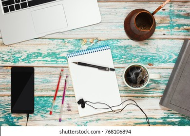 Working desk of studen or freelance person. Office accessories such as pens and note pad and gadgets and traditional turkish coffee pot on loft style rough wooden background  Top view.