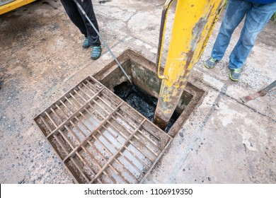 Working for drain cleaning. Problem with the drainage system. worker with cleaning truck pumps out the dredging drain tunnel cleaning sewage in city street.