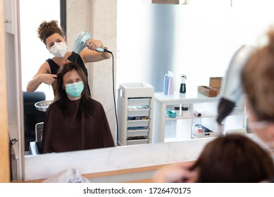 Working during covid-19 or coronavirus concept. A professional hairdresser cutting the hair to a client, reflected in the mirror with copy space.
