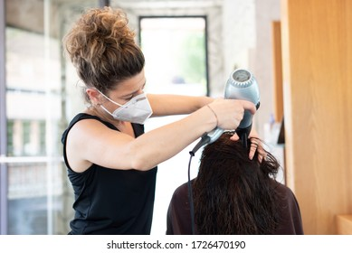 Working during covid-19 or coronavirus concept. Hairstylist drying the hair of a client in a beauty center.
