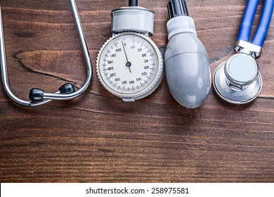 working elements of blood pressure monitor and stethoscope  on vintage wooden board horizontal version medical comcept