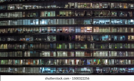 Working evening in glass business centre office building with numerous offices with glass walls and illuminated windows timelapse. People sitting at desks. Pan right