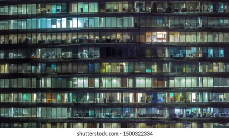 Working evening in glass office building with numerous offices with glass walls and illuminated windows timelapse. People sitting at desks. Zoom out