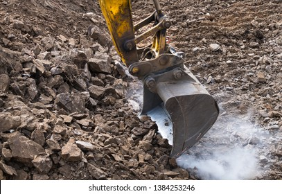 Working excavator bucket. Sparking. Dusty construction site. Digger machine. Excavation work. Power shovel moving soil and stones. Digging building foundations in rock. Earth mover. Civil engineering.