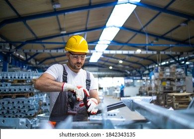 Working in factory assembling parts in production line.