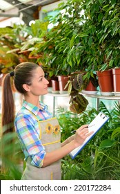Working in greenhouse. Beautiful woman in uniform writing something in her note pad and looking at the flowers while standing in greenhouse