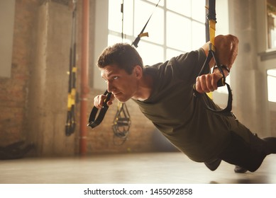 Working hard. Side view of young and strong athletic man in sportswear doing push ups with trx fitness straps in the gym.