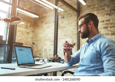 Working hard. Thirsty bearded businessman in eyeglasses and formal wear drinking fresh water and looking at laptop while sitting in the modern office