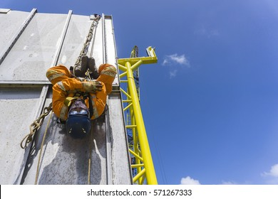 Working at height. An abseiler complete with Personal Protective Equipment (PPE) and fall arrestor equipment hanging downside at the edge of oil and gas platform structure with background blue sky.