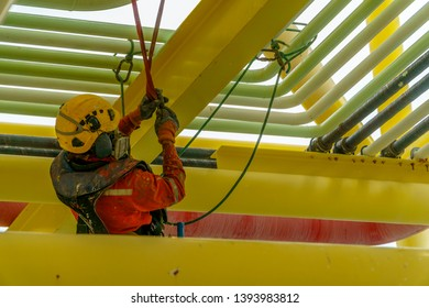 Working at height. An abseiler with orange coverall wearing Personal Protective Equipment (PPE) hanging under pippeline using abseiling technique.