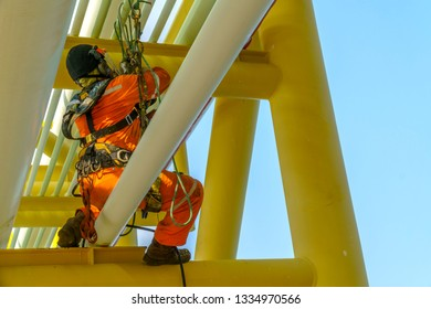Working at height. An abseiler from rear view with dirty coverall wearing Personal Protective Equipment (PPE) hanging at life lines sitting on pipeline managing his rope access.