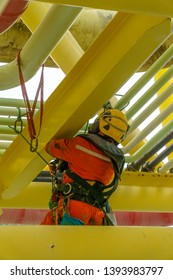 Working at height. An abseiler from rear view with dirty coverall wearing Personal Protective Equipment (PPE) hanging at life lines for painting activities at pippeline using abseiling technique.