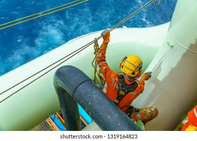 Working at height. An abseiler wearing complete Personal Protective Equipment (PPE) sitting on gas pipeline for painting activities.