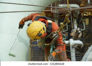 Working at height. Aerial view of an abseiler wearing Personal Protective Equipment (PPE) hanging at pipeline for painting activities.