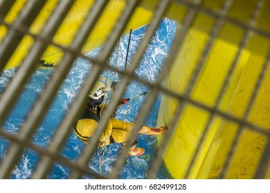 Working at height. A commercial abseiler with fall arrestor device doing coral removal using high pressure water. Blurred foreground of galvanized grating.