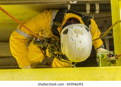 Working at height. A commercial abseiler with fall arrestor device doing painting inspection on oil and gas platform.