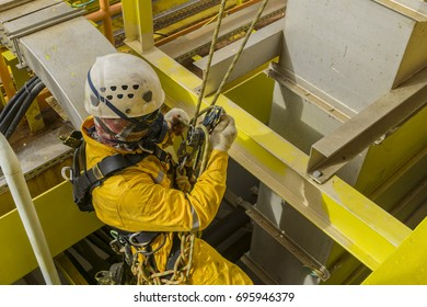Working at height. A commercial abseiler with Personal Protective Equipment (PPE) secure his fall arrestor during hanging on oil and gas platform structure