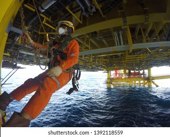 Working at height. A commercial abseiler with respiratory protection, work vest and fall arrestor device hanging under oil and gas structure platform.