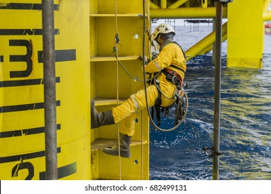 Working at height. A commercial abseiler with respiratory protection and fall arrestor device hanging on oil and gas platform jacket module to clean rust using air grinding machine.