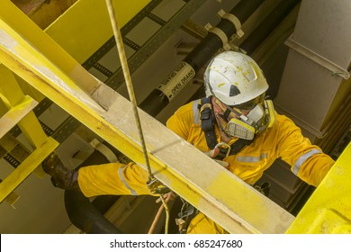 Working at height. A commercial abseiler with respiratory protection and fall arrestor device doing painting inspection on oil and gas structure platform.