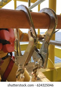 Working at height. Fall arrestor device or safety body harness for people working at height complete with double lanyard and hooks locked at handrail with selective focus.