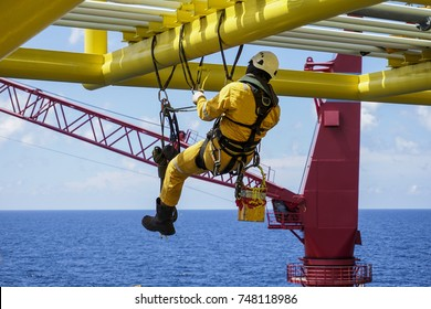 Working at height. Working overboard. A commercial abseiler with fall arrestor device hanging on bridge pipeline structure at oil and gas platform to perform painting works.