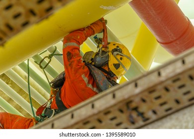 Working at height using abseiling technique. Rear view of an abseiler with fall protection hanging under pipeline rack.