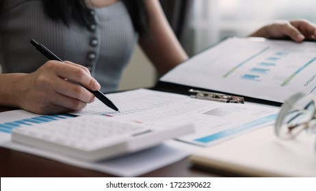 Working from home, Closeup business woman using calculator and analyzing financial report, work from home concept