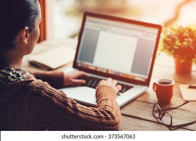 Working at home. Close-up image of young woman working on laptop while sitting at the rough wooden table