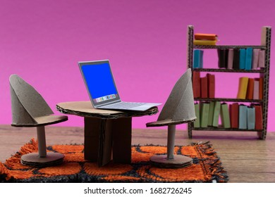 Working from home concept. Cardboard furniture in a doll house with a table and chairs on a rug.  Paper laptop op the table. Book case in the background. Pink background. Room for copy.