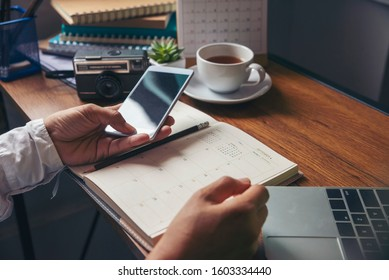 Working from home concept. Planner using phone and laptop to plan daily agenda on calendar book. Woman mark and noted schedule (holiday trip) on diary at home office desk. Coffee place on table.