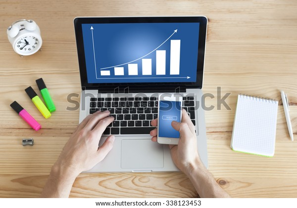 Working at home on business charts with laptop and smartphone