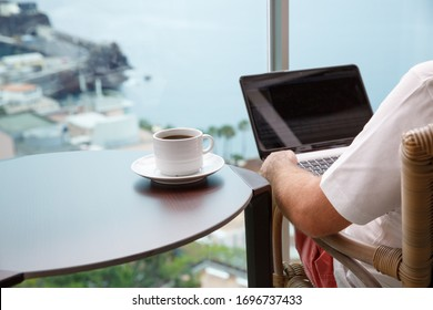 Working from home. Workplace with laptop and cup of coffee on balcony overlooking ocean.