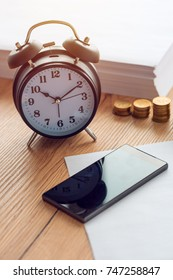 Working hours, vintage clock and mobile phone on business office desk