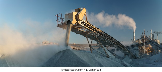 Working industrial equipment of a crushing and processing plant in a plume of white stone dust, panorama.