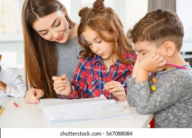 Working with kids. Beautiful young female teacher with her little students at the classroom education children childhood school profession job occupation knowledge lessons helpful smart concept