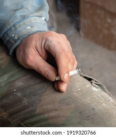A working man holds a cigarette. Close-up