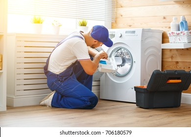 working man plumber repairs a washing machine in   laundry