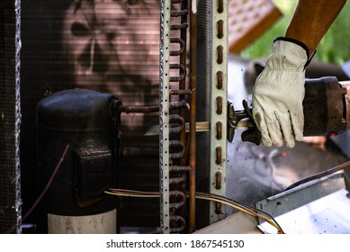 Un ouvrier utilisant un Sawzall pour couper les bobines d'une unité HVAC afin de recycler les matériaux dans un dépôt de ferraille. métal, cuivre, condensateur, compresseur.