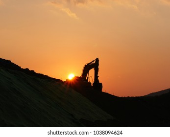 Working mechanical excavator silhouette in sunset