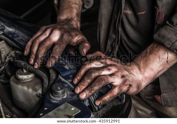 Рабочие люди с грязными руками остаются рядом с двигателем автомобиля