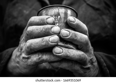 Working men's hands. A man holds a metal mug in his hands.